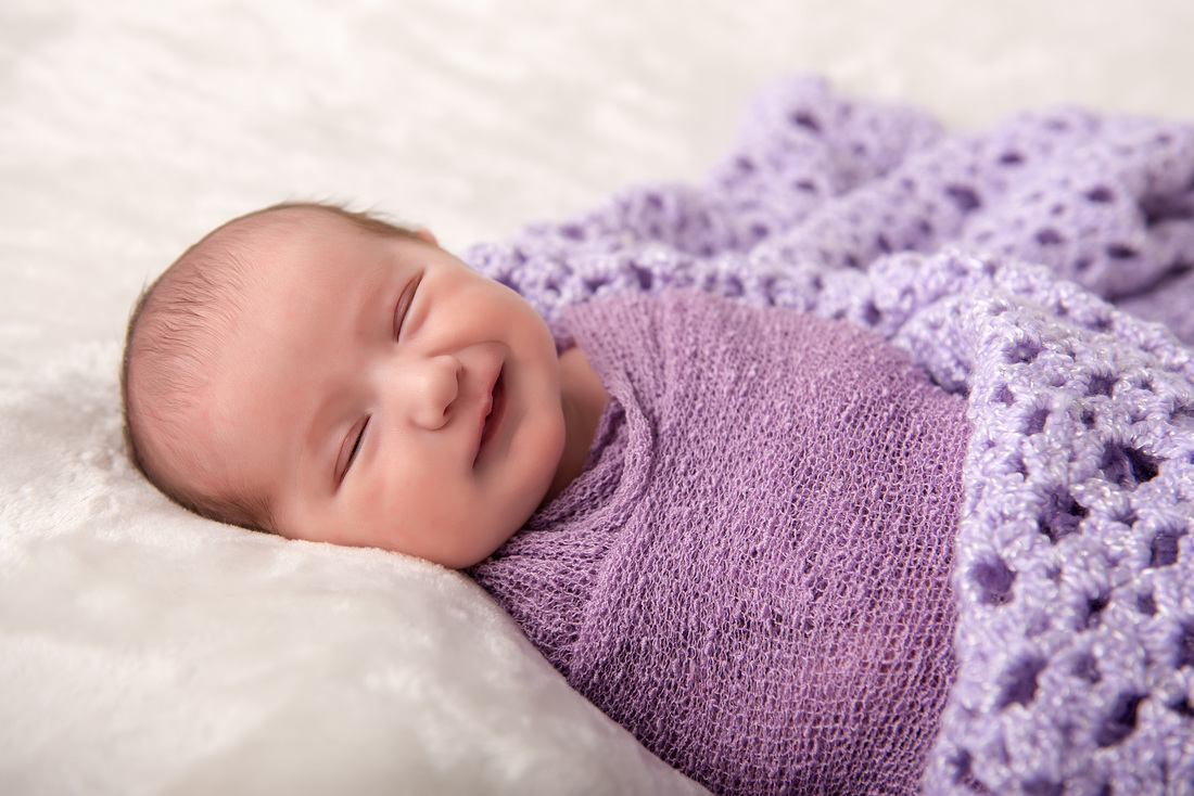 smiling newborn girl in purple
